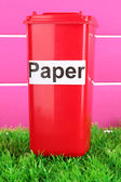 Recycling bin on grass on pink background — Stock Photo
