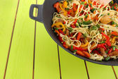 Noodles with vegetables on wok on wooden background — Stock Photo