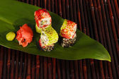 Tasty Maki sushi - Roll on green leaf on bamboo mat — Stock Photo