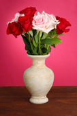 Beautiful bouquet of roses in vase with gift on table on pink background — Stock Photo