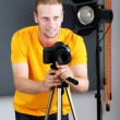 Handsome photographer with camera at working, on photo studio background — Foto de Stock