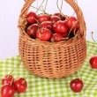 Cherry berries in wicker basket on wooden table close up — Stock Photo