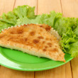 Tasty chebureks with fresh herbs on plate,on wooden background — ストック写真