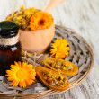 Medicine bottle and calendula flowers on wooden background — Stock Photo