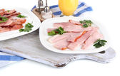 Bacon on plates on napkin on board isolated on white — Stock Photo