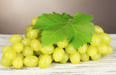 Ripe delicious grapes on table on gray background — Stock Photo