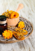 Medicine bottle and calendula flowers on wooden background — Stock Photo