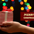 Woman hand with gift box, on garland background — Stock Photo