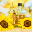 Stock Photo: Oil in jars and sunflower on wooden table close-up