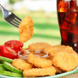 Fried chicken nuggets with vegetables,cola and sauce on table in park — Lizenzfreies Foto
