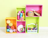 Colorful shelves of different colors with utensils on wall background — Stock Photo