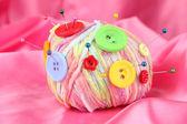 多彩按钮和多色羊毛球,彩色织物背景上 — 图库照片
