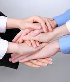 Group of young people's hands on gray background — Stockfoto