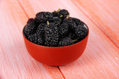 Ripe mulberries in bowl on wooden background — Stock Photo