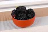 Ripe mulberries in bowl on table in room — Stock Photo
