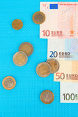 Euro banknotes and euro cents on blue background — Photo