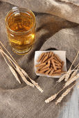 Beer in glass and crackers on bagging on wooden table — Stock Photo