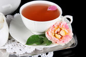 Cup of tea from tea rose on metallic tray on napkin black background — Stock Photo