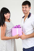 Beautiful loving couple with gift on grey background — Stock Photo