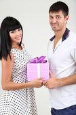 Mooie verliefde paar met gift op grijze achtergrond — Stockfoto