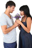 Beautiful loving couple with flowers isolated on white — Stock Photo