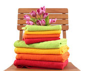 Towels and flowers on wooden chair isolated on white — Stock Photo