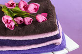 Towels and flowers on wooden chair on purple background — Stock Photo