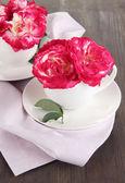 Rose in tazze sul tovagliolo su fondo in legno — Foto Stock