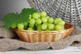 Ripe delicious grapes in wicker basket on table on gray background — Stock Photo