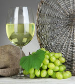 Ripe delicious grapes with glass of wine on table on gray background — Stock Photo