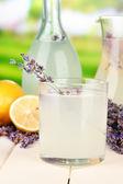Lavender lemonade in bottle and jug, on bright background — Stock Photo