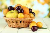 Frutas de verano brillante en cesta en mesa de madera sobre fondo natural — Foto de Stock