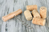 Corkscrew with wine corks on wooden table close-up — Stock Photo