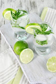 Glasses of cocktail with ice on board on napkin on wooden table — Stockfoto