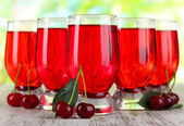 Glasses compote on wooden table on nature background — Stock Photo
