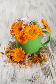 Calendula flowers in cup on wooden background — Stock Photo
