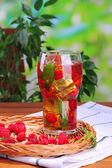 Iced tea with raspberries and mint on wooden table, outdoors — Stock Photo