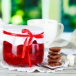 Stock Photo: Yummy jam in bank on napkin on wooden table on window background