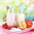 Delicious milk shakes with strawberries and peach on wooden table on natural background — Foto de Stock