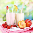 Delicious milk shakes with strawberries and peach on wooden table on natural background — Стоковая фотография