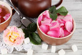 Kettle and cup of tea from tea rose on board on napkin on wooden table — Stock Photo