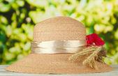 Krásné letní klobouk s kytičkou a klásky na zeleném pozadí — Stock fotografie