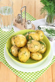 Boiled potatoes on platens on on napkins on wooden table — Stock Photo