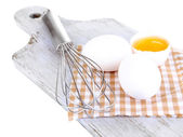 Corolla and eggs on wooden board isolated on white — Stock Photo