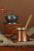 Metal turk and coffee beans on brown background — Stock Photo