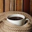 Cup of coffee wrapped in scarf on books background — Foto Stock #28087101