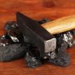 Coal with hummer on wooden background — Stock Photo #28087399