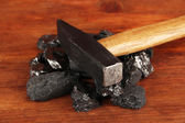 Coal with hummer on wooden background — Stock Photo