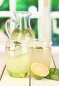 Citrus lemonade in pitcher and glasses on wooden table on window background — Stock Photo