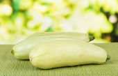 Fresh marrows on bamboo mat, on bright background — Stock Photo